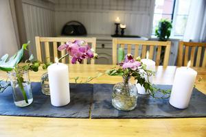 I vaser på köksbordet har Cecilia stuckit ner kvistar av murgröna, monstera och orkidéer.