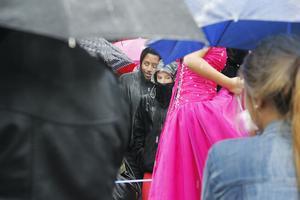 Vackra klänningar, smink och hår skyddades under paraplyer.