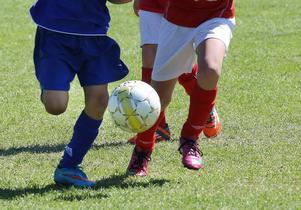 Bollduell mellan barn som spelar fotboll.