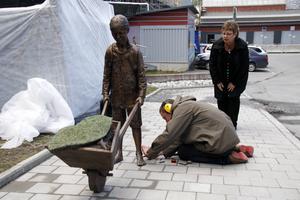 Konstnären Knutte Wester stansar in signatur och årtal i den nyss avtäckta skulpturen. Landstingsrådet Harriet Jorderud (S) tittar på.
