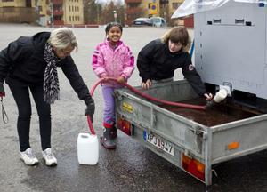 Monica Norin, Diana Semére och Jon Lindgren hämtade vatten ur tanken på Blockvägen.