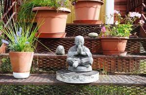 Blommor i klassiska svenska lerkrukor, och indiska dekorationer, trängs i en av de gamla trapporna på gården.