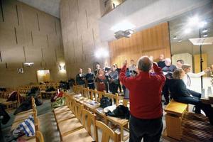 Sista repetitionen i Hornsbergskyrkan inför de båda konserterna i helgen. Henry Åkerlund manar på sina sångare i Octava.