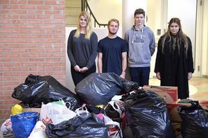 Lina Söderberg, Per Martelleur, Philip Nilsson och Hanna Fahlander framför den stora mängden kläder de lyckats samla in till stadens hemlösa.