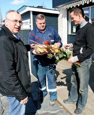 Bo Holmberg, elmontör och Anders Byström, projektledare, lämnar blommor till Mats Åhman, den 7 000:e kunden som fått sin mätare utbytt.