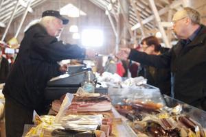 Bengt Wikberg bjuder besökare på smakbitar av korv och rökt sidfläsk.
