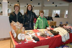 Tona Berglund med sönerna Rasmus och Viktor Bergström säljer enbärsdricka och allt annat som hör till ett loppisbord.