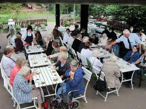 Sällskapet sitter och dricker eftermiddagskaffe i Säterdalen. Busschauffören Jan Vikström rycker ut och hjälper cafépersonalen att servera kaffe.