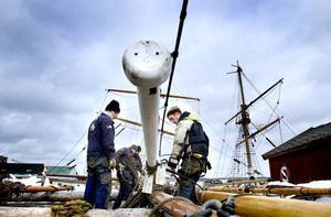 Att sätta upp en toppmast 30 meter upp i luften är inget som görs på en kafferast. Manövern förbereds noga på marken innan kranen tar vid. Riggarbetarna Jonas Ottosson och Joakim Ekedahl syns närmast i bild.