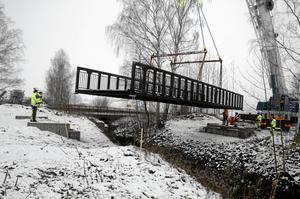 Bro på väg. Det krävdes en rejäl lyftkran för att få den 17 ton tunga bron på plats över Pryskebäcken. Bild: Lars-Ivar Jansson