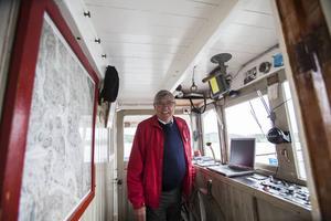 Skepparen Per-Erik Kristoffersson styr ångbåten Alma med god hjälp av sjökort på nymodigheter såsom en bärbar dator.