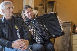 Edvin Sundström lyssnar på Erik Brun som spelar några låtar på dragspel.