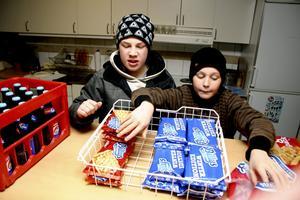 Emanuel Fahlström och Daniel Berggren hjälper till med pizzan och läsken.