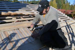 Peter Svensson spikar ny pert på taket vid Lisskvarngården.