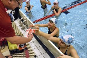 Kortutdelning. Mats Jansson delar ut kort som visar hur mycket ungdomarna ska simma.