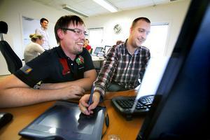 Ola Engman och Sebastian Österman diskuterar en webb-sida.