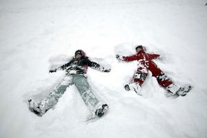 Ella och Felicia, 7, kastar sig i snön och gör änglar.