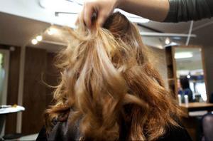 När hela håret är lockat och det har svalnat drar Kristina försiktigt fingrarna genom det.
