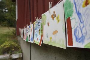 Alla teckningar hängs på rad längs med husväggen.