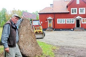 Johan Clarholm vid stenen som är tänkt att bli en ny runsten. I bakgrunden järnvägshuset i Röjan som han ägnat flera år till att rusta upp.