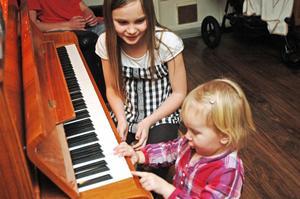 """Beda Dillner, 8 år, har lärt sig att spela piano på egen hand. Hon spelar även blockflöjt på kulturskolan. Flora Dillner, 2 år, brukar också klinka lite. """"Men det är applåderna som är det viktigaste för henne"""", säger mamma Lotta."""