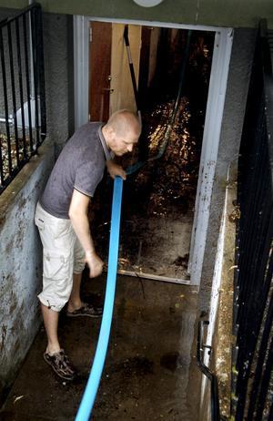 """Efter skyfall. """"Jag brukar syssla med bredband, men nu får alla på Libo hjälpa till med vattnet"""", säger Markus Hjalmarsson. På Siggebohyttevägen hade vattnet letat sig ned vid källartrapporna."""