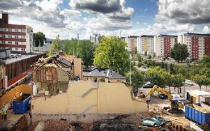 Man ser rätt in i huset som rivs i Borlänge. En grävskopa river väggen ut mot Ovanbroparkeringen samtidigt som folk jobbar uppe på taket. Foto: Staffan Björklund