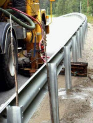 Skrapan går in under vägräcket och rensar bort sandvallarna så att vattnet kan rinna av vägen. Den fjädrar automatiskt tillbaka vid varje stolpe.