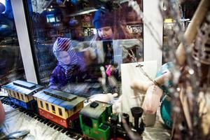 Där Fantasi blir verklighet. Judith Klack Turner, 7, och systern Villemo, 10, tittar på det elektriska tåget som tuffar fram mellan granar med snötyngda grenar. Leksaksbutikens julskyltning lockar både barn och vuxna.