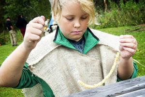 Linus arbetade med ett halsband smyckat av fiskkotor.