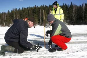 Mikael Högdahl, Ivar Helenius och Niklas Asplund hjälps åt att mäta upp 400 rutor på isen som ska fördelas mellan lagen.