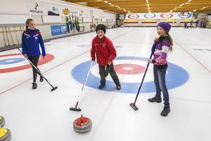 Sundsvalls curlings Emmy Landberg instruerar David och Ylva Öhlén som tyckte att det svåraste var att få stenen att glida rakt.