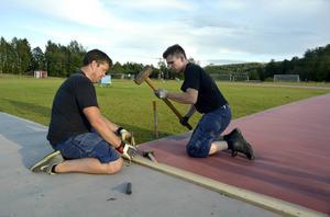 Från vänster Mattias Strand och Patrik Wallgren som gör fast mattor som besökarna kan gå på.