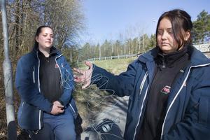 Emma Malmström (till vänster) skadades i ansiktet. Matilda Hyle visar ståltråden som satt uppsänd över cykelbanan.