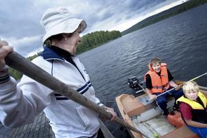 Rektor och förste båtshakare. För fjärde sommaren i rad är Smedjebackens särskolebarn nu på läger. Platsen är Nyckelön i Barken och där är nu 15 barn och ungdomar med ledare på plats sedan onsdag. Olika aktiviteter och lekar finns för deltagarna - populärast är kanske fisket. Ulla Norin som här håller in ekan åt två av fiskarna är en av de frivilliga ledarna på ön. Foto:Karin Rickardsson