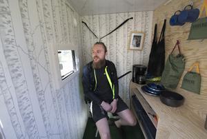 Lite trångt, men väldigt mysigt. Christoffer sover på ett liggunderlag på golvet i cykelhuset och lagar sin mat på långbänken som har förvaring under.