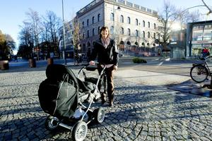 Lena Bergander som kör sitt barnbarn i en vagn välkomnar bussförbudet.  – Varför ska de köra här när det finns massor av vägar runt torget? Det har känts konstigt med en gångyta där man måste se upp för bussar, säger hon.