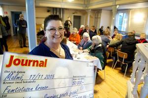 Manuela Lampe med checken på 50 000 kronor. Pengarna använder hon klokt genom att sätta in dem på skattekontot.