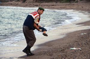 En turkisk polis bär bort den döde pojken från stranden nära den turkiska turistorten Bodrum. Pojken är en av minst tolv syrier som drunknade när två båtar förliste under försöket att nå den grekiska ön Kos. På bilder som spreds via nyhetsbyrån Reuters syns hur en pojke spolats upp på stranden. I turkiska medier identifieras han som treårige Aylan från Kobanae.