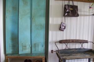 Den gamla kuskbänken är en av Isabellas favoriter. Hon fyndade den på loppis och sedan har hon satt ben från en stol på den. Nu står den i hallen. Plåtskåpen stod i en lada på gården men Isabella har målat dem.