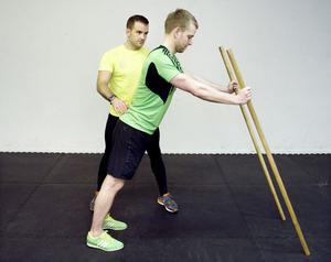Träna ihop med en kompisDe här övningarna är funktionella, det vill säga de aktiverar många muskelgrupper samtidigt och man rör sig över flera leder. Det ger en allsidig träning, då stora delar av kroppen får sig en genomkörare i samma övning, även pulsen går upp och konditionen tränas. Varje övning bör upprepas 15 till 20 gånger med bibehållen hållning. Medan du tränar står kompisen bredvid och kontrollerar hållningen och assisterar enligt bildtexterna. Alternera sedan.Axel Sjöstedt och Marcus Nordahl tränar tillsammans. Med en träningskompis är chansen större att det blir av.1. Triceps med käppHåll två käppar (cirka tre centimeter i diameter) som stavar framför dig med händerna i brösthöjd. Låt hållningen vara neutral och spänn magen och rumpan. Fall ner så att huvudet kommer i höjd med händerna. Pressa dig tillbaka upp till utgångsläget med bibehållen hållning.Du tränar: Triceps (baksidan av överarmen), magen, höftböjaren.