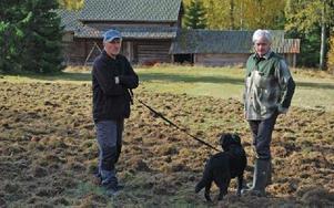 Sven Liss med hunden Molle och Anders Sjölund från Ljusbodarnas fäbodlags styrelse inspekterar skadegörelsen. Foto: Annki Hällberg