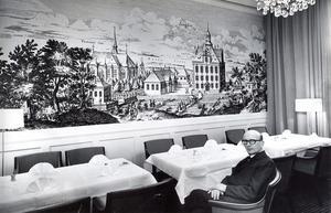 14 december 1966. Lars Lindblom i en fåtölj i stadshotellets nya Arosrum. På väggarna förstoringar av västmanländska slott, som hans firma framställt. 2,40 meter gånger 5,60 meter meter är denna den största väggen med Ängsö slott. Den består av tolv sammanfogade bitar. Originalet - ett bilderboksblad.