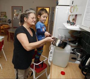 Förskoleläraren Annika Lago får hjälp av Riccardo med tappa det kokta vattnet i dunkar.