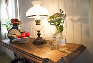 Avlastningsbordet i köket är tillverkat av en gammal skiva som de hittade i ladugården och ett underreda till en symaskin. Den gamla fotogenlampan som utrustats med el kommer från Marias föräldrar och i apoteksflaskorna står kärleksört och vallmo.