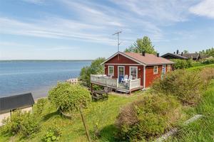 Mindre stuga i Bullås med havsutsikt och stranden utanför knuten.