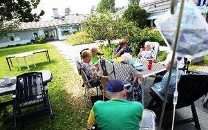 På Korsnäsgården siter en grupp under ett träd och dricker kafffe och äter tårta. FOTO: ANNIKA BJÖRNDOTTER