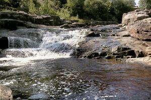 Vattnet skummar och fräser och kastar sig ner mellan stenarna i älvfåran. I de lugnare partierna glittrar det förföriskt i solen.