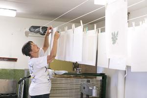 Gunilla Unnes hänger upp nytillverkade papper på tork.