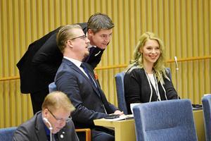 Hanna Wigh (SD) i riksdagen intill partikollegorna Linus Bylund och Oscar Sjöstedt.
